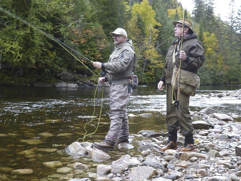 Le guide Sylvain Gagnon (avec la casquette) initie le pêcheur Michel Brabant à la pêche à la truite bleue. (Photo Pierre Gingras, La Presse)