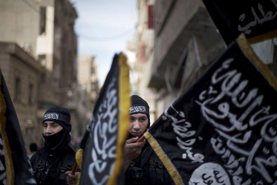 Des militants islamistes brandissent des drapeaux du Front... (PHOTO ARCHIVES AFP)