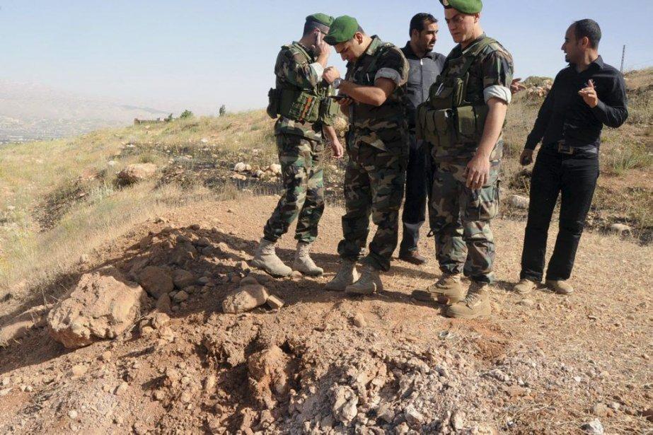Des soldats inspectent le cratère causé par le... (Photo AFP)