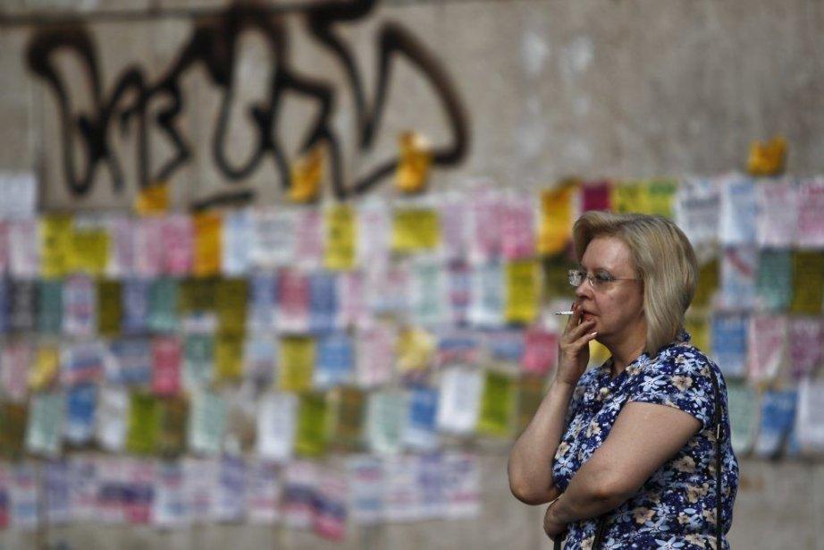 À Moscou, une femme fume une cigarette la... (PHOTO MAXIM SHEMETOV, REUTERS)