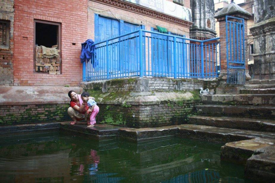 Une dame lave le visage de son enfant... (Photo NAVESH CHITRAKAR, Reuters)