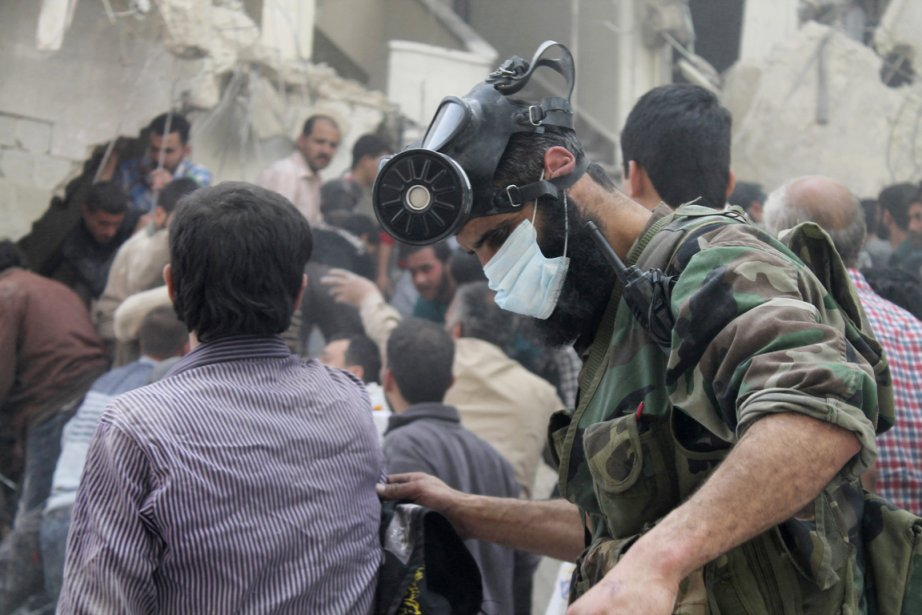 Un homme muni d'un masque à gaz recherche... (PHOTO HALEEM AL-HALABI, ARCHIVES REUTERS)