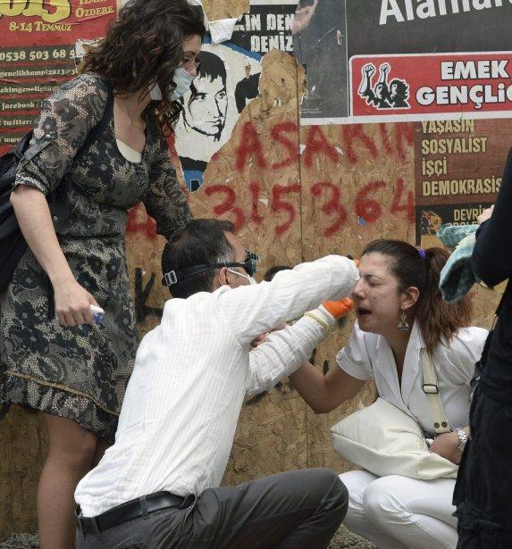 Une manifestante reçoit l'aide d'un autre manifestant après avoir été blessée à Ankara. | 6 juin 2013