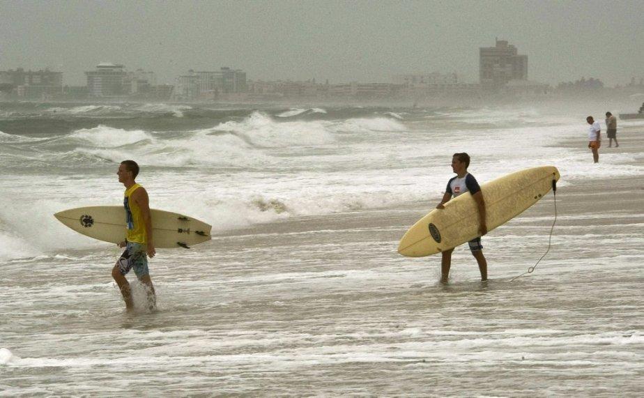 Les surfers profitent des vagues alors que le... (Photo STEVE NESIUS, Reuters)