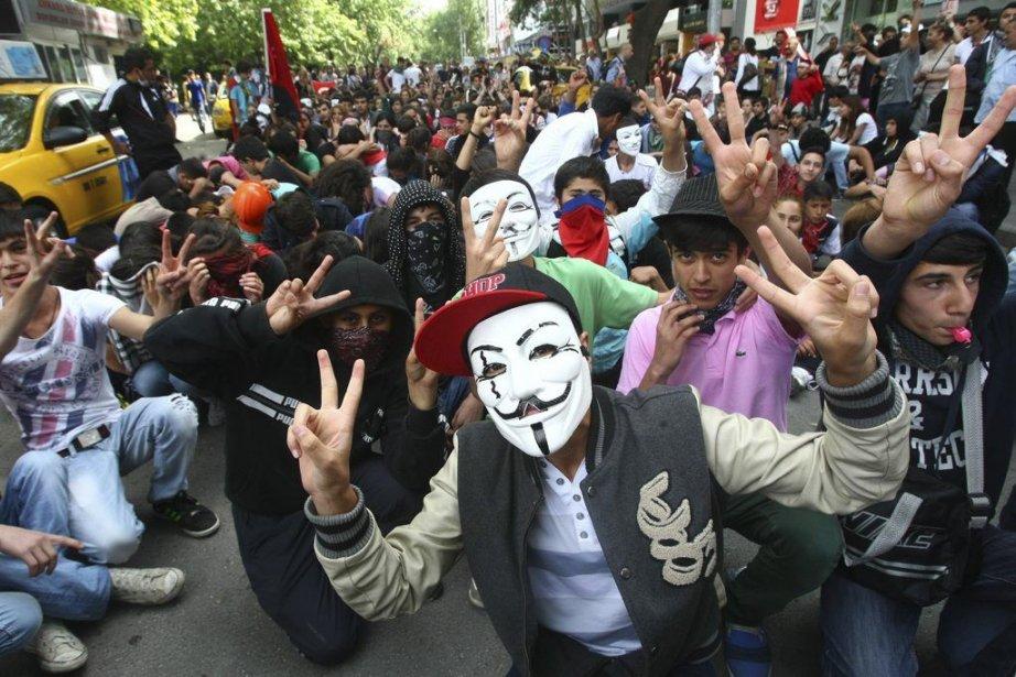 Des protestataires turcs portant des masques manifestaient pacifiquement... (PHOTO ADEM ALTAN, AFP)