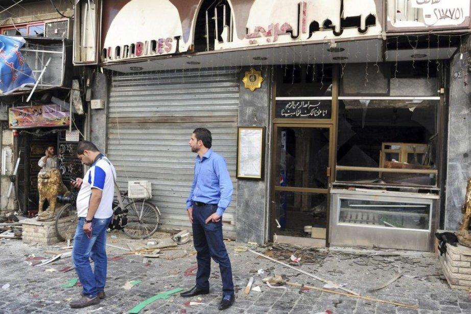 Deux syriens debout devant les dommages causés par... (PHOTO SANA, AFP)