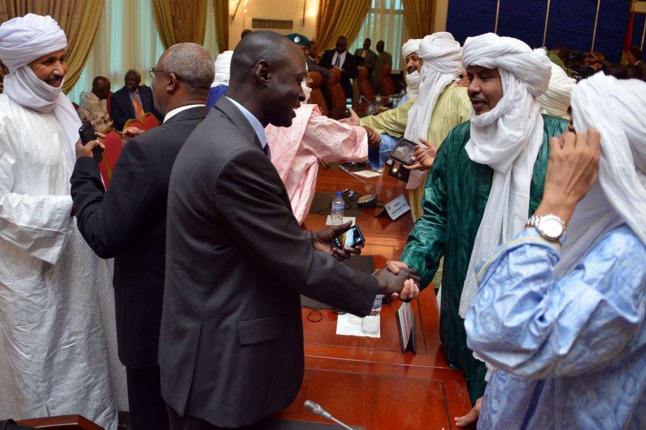 Les membres des délégations malienne et touareg se... (PHOTO AHMED OUOBA, AFP)