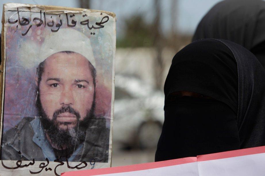 Un protestataire portant le niqab montre une photo... (PHOTO REUTERS)