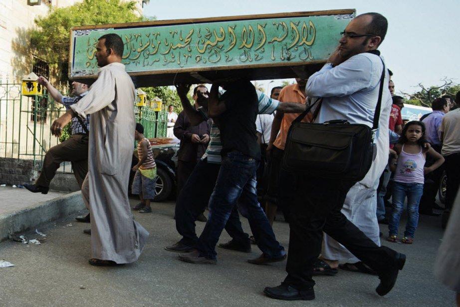 Des hommes transportent le cercueil d'une des victimes... (PHOTO GIANLUIGI GUERCIA, AFP)