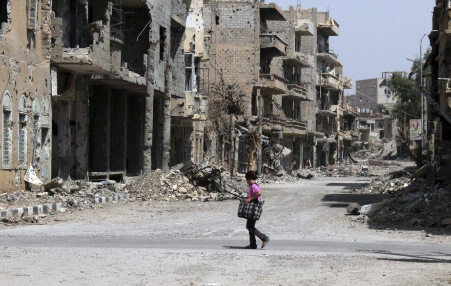 Une fille traverse la rue à Deir Ezzor,... (Photo ABO SHUJA, AFP)