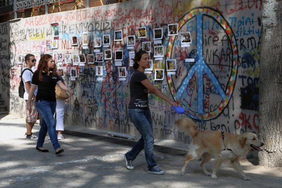 Des passants marchent devant une murale de photos... (Photo Burhan Ozbilici, AP)