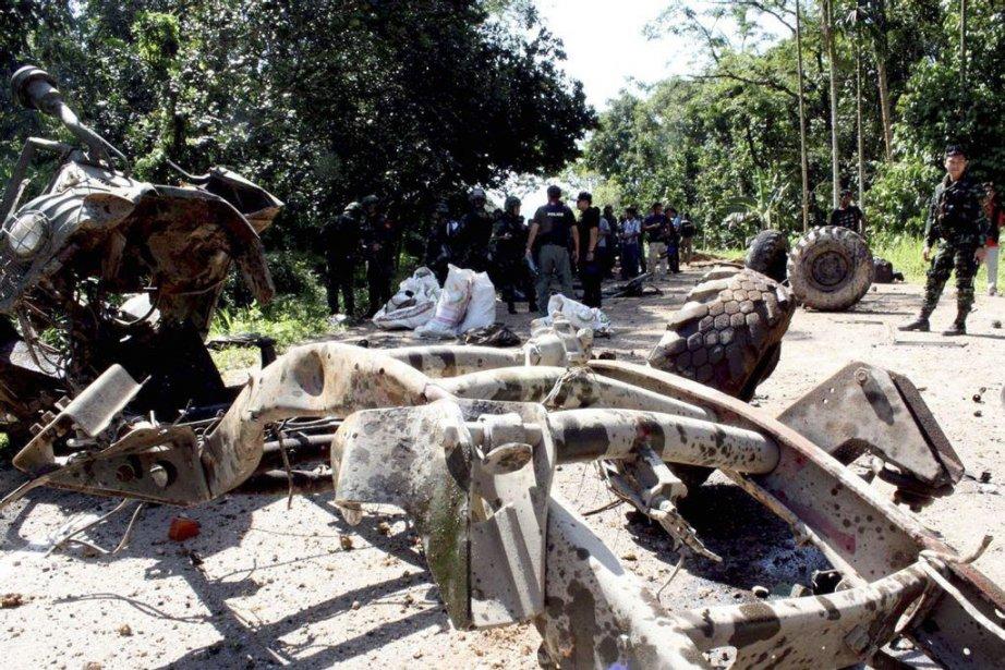 Des soldats thaïlandais examinent le site où un... (Ahmad Ramansiriwong)