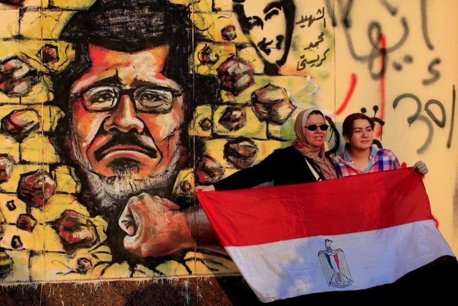 Deux femmes brandissent un drapeau égyptien devant un... (Photo Hassan Ammar, AP)