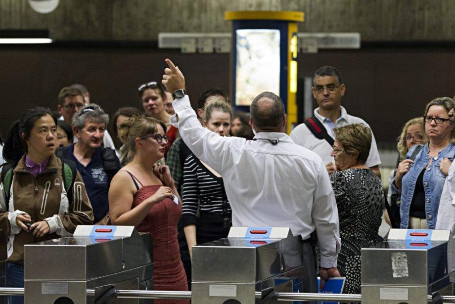 Un employé de la STM explique la situation aux usagers du métro. (PHOTO ANNE GAUTHIER, LA PRESSE)
