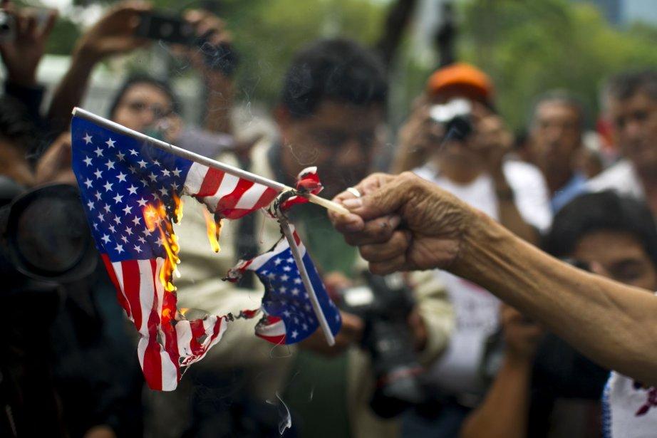 Une femme brûle le deapeau américain en support...