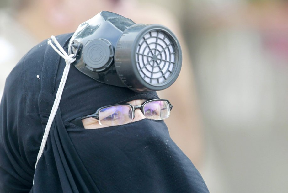 Une partisane des Frères musulmans porte un masque à gaz par dessus son niqab, alors qu'elle participe à une manifestation devant le quartier général de La Garde républicaine, au Caire, où l'ex-président Morsi aurait été détenu. | 9 juillet 2013
