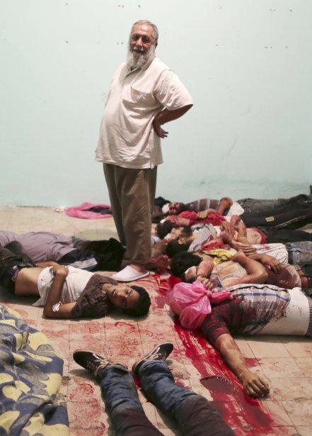 Un homme se tient au milieu de corps ensanglantés dans un hôpital en banlieue du Caire, le 8 juillet. L'armé égyptienne a ouvert le feu, hier, sur la foule, composée de partisans de l'ex-président Morsi, tuant au moins 51 personnes. | 9 juillet 2013