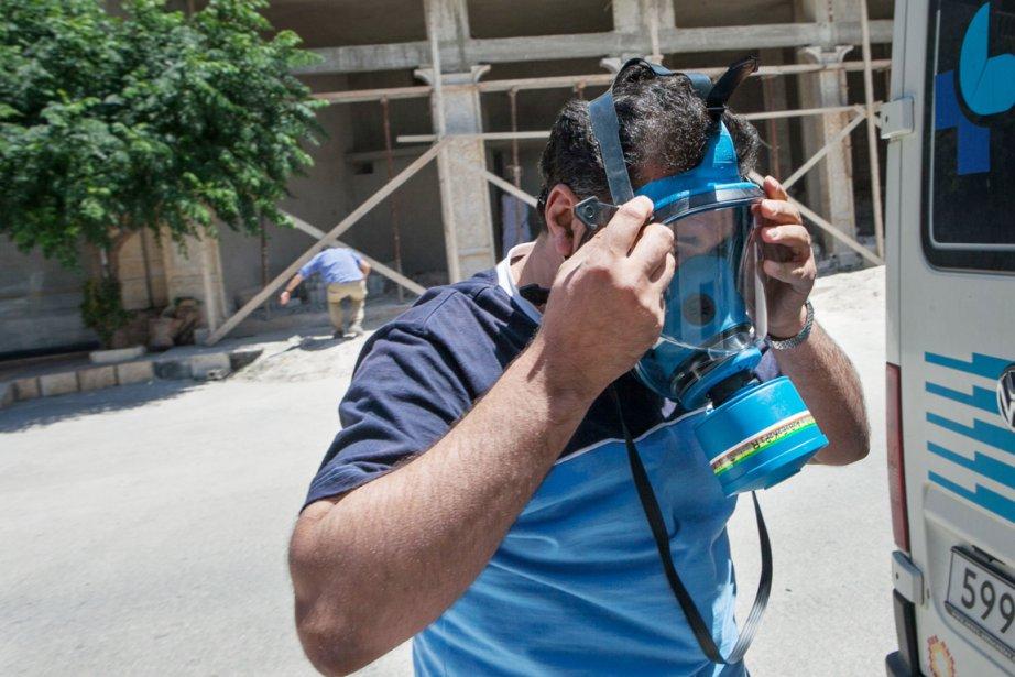 Un ambulancier civil enfile un masque à gaz... (PHOTO DANIEL LEAL-OLIVAS, AFP)