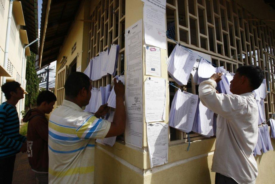 Des citoyens cherchent leurs noms sur les listes... (Photo Heng Sinith, AP)