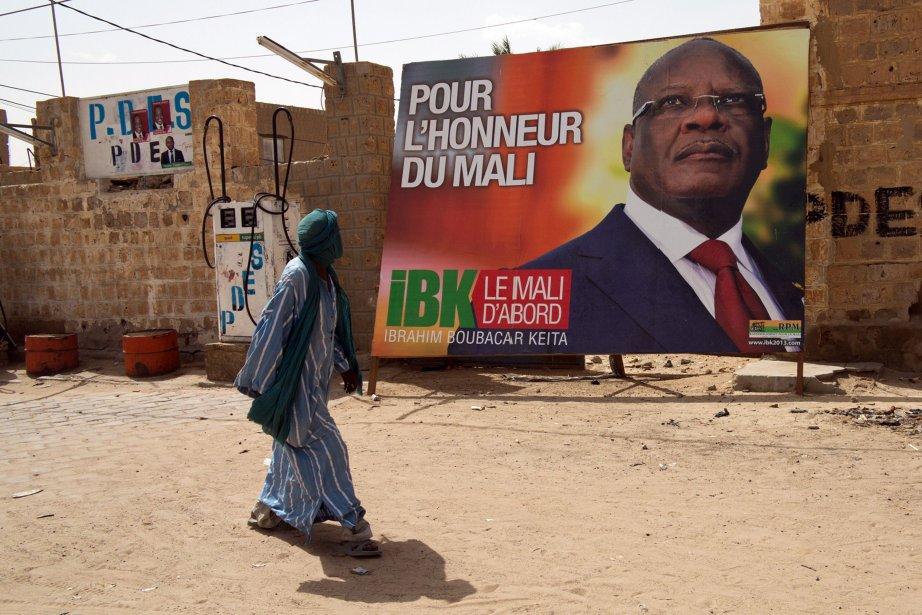 Un homme passe devant la photo du candidatIbrahim... (PHOTO DOROTHEE THIENOT, AFP)