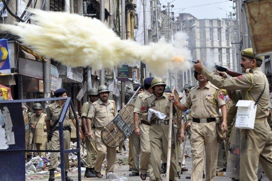Un policier indien tire du gaz lacrimogène sur... (PHOTO AFP)