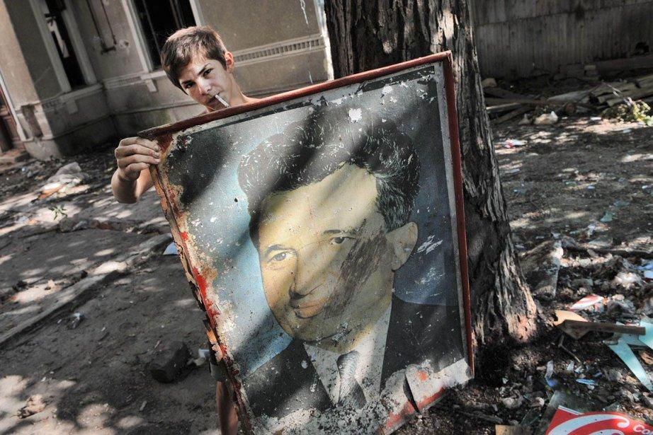 Une femme tient une image de l'ancien dictateur... (Photo Archives AFP)