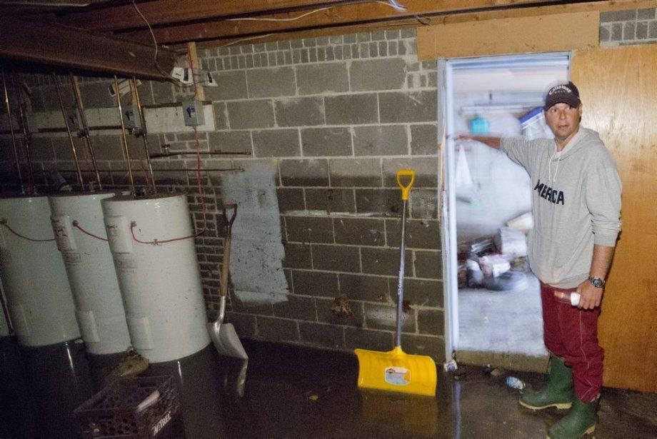 Martin Comeau, dont la famille est propriétaire de l'immeuble, indique le niveau de l'eau dans le sous-sol. | 14 août 2013