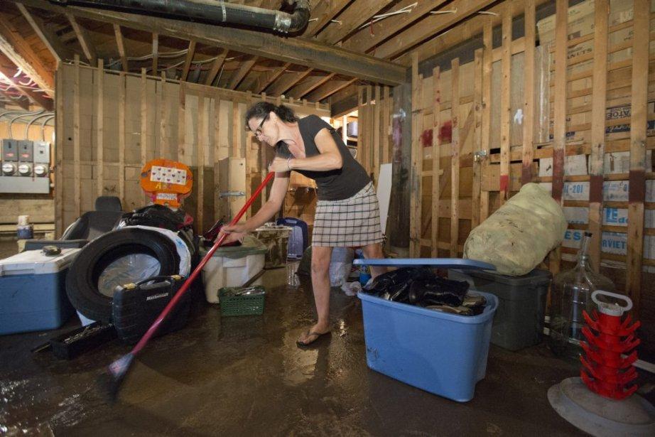 Une locataire nettoie les dégâts causés par un refoulement d'égout suite à des pluies diluviennes la nuit précédente. | 14 août 2013