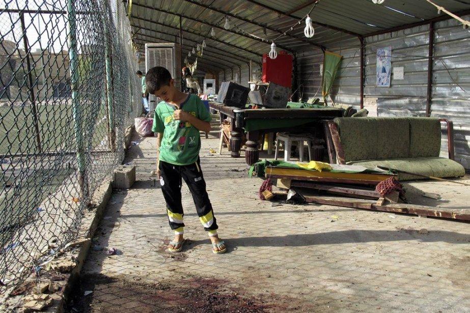 Un jeune garçon regarde une marre de sang... (PHOTO AHMED MALIK, REUTERS)