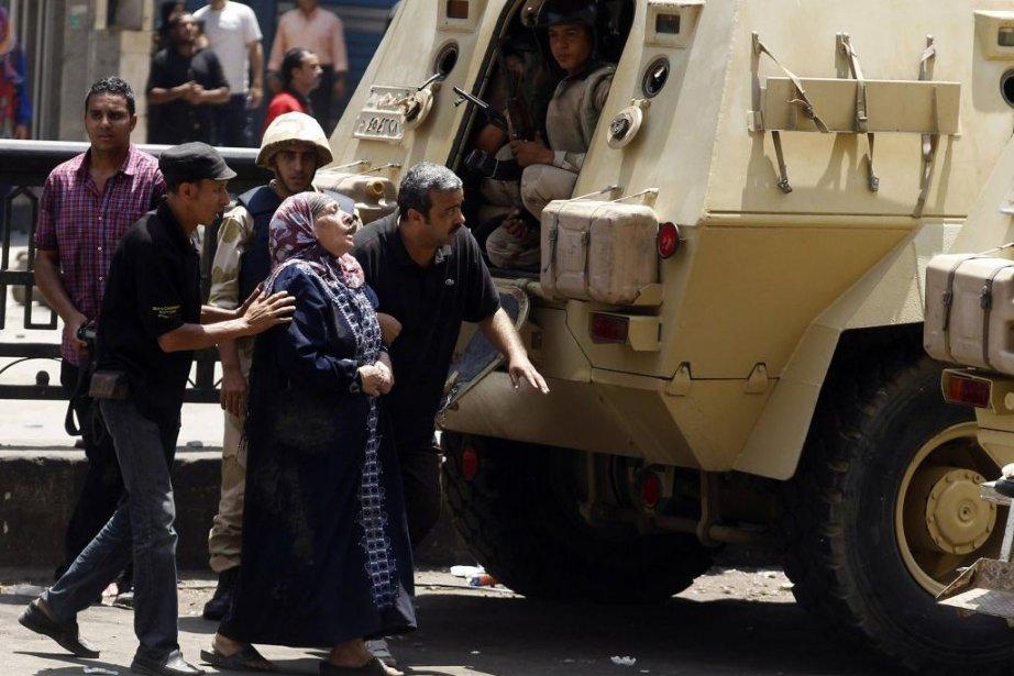 Une femme est escortée par la police à... (PHOTO AMR ABDALLAH DALSH, REUTERS)