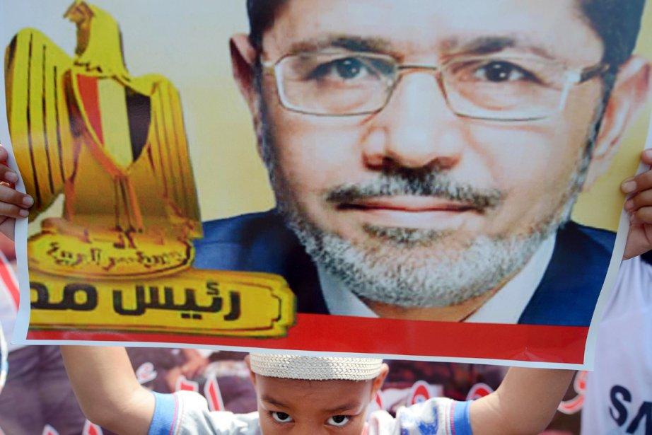 Un jeune partisan du président déchu brandit une... (PHOTO ADEK BERRY, AFP)