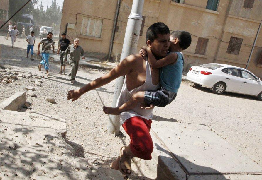 Un homme court avec un jeune garçon dans ses bras, alors que des civils d'un village de la province de Raqqa, dans l'est de la Syrie, fuient à l'annonce de frappes de l'aviation syrienne. | 21 août 2013