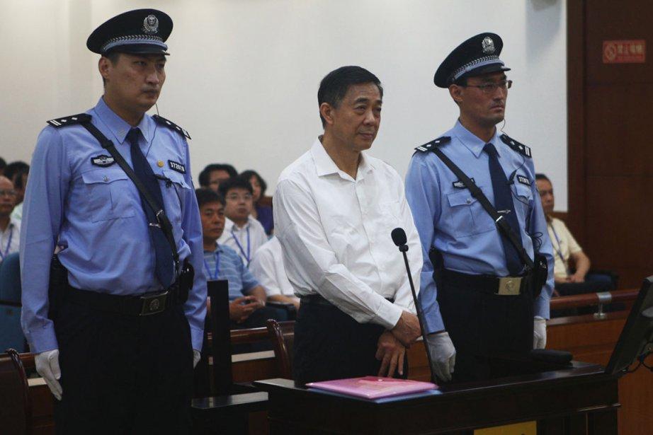 Encadré par deux policiers, habillé d'une chemise blanche... (PHOTO REUTERS)
