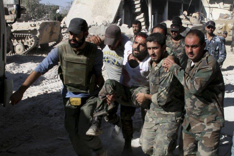 Des soldats de l'armée syrienne transportent un des... (PHOTO KHALED AL-HARIRI, REUTERS)
