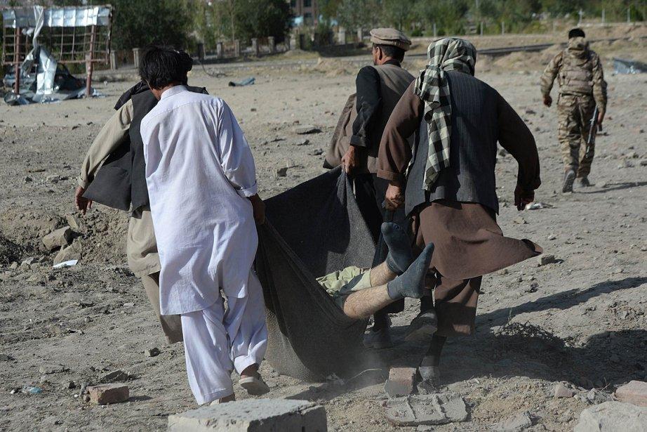 Des Afghans transportent le cadavre d'un des rebelles... (PHOTO SHAH MARAI, AGENCE FRANCE PRESSE)