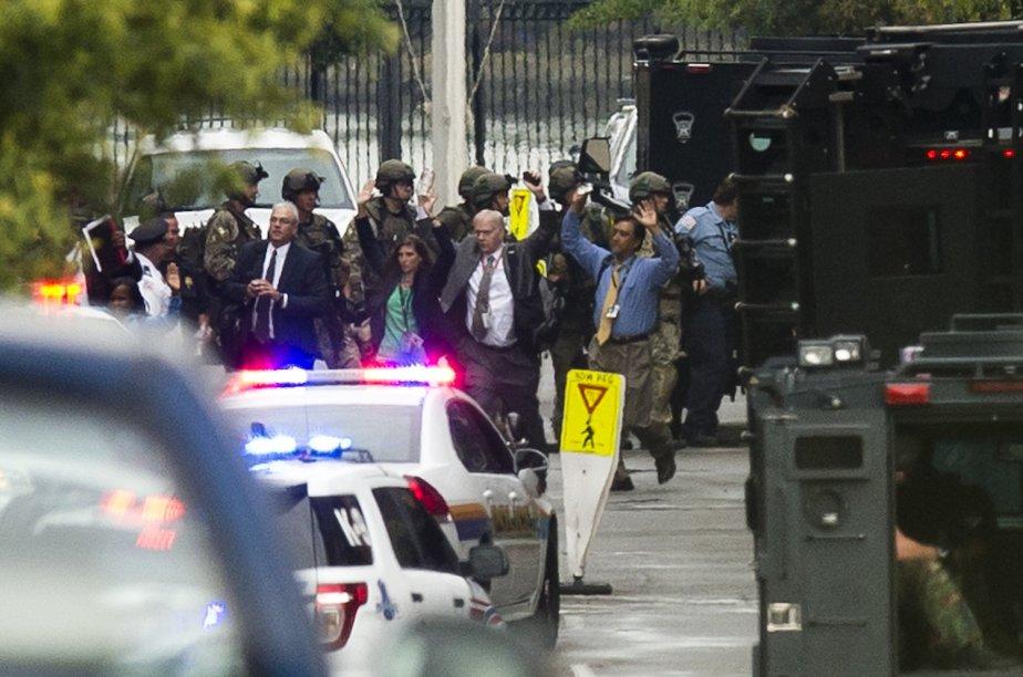 Des employés qui se trouvaient à l'intérieur d'un des édifices sont évacués, les mains sur la tête, selon les ordres des policiers. Au moins un policier a été touché dans un échange de feu avec le tireur qui a été abattu. | 16 septembre 2013