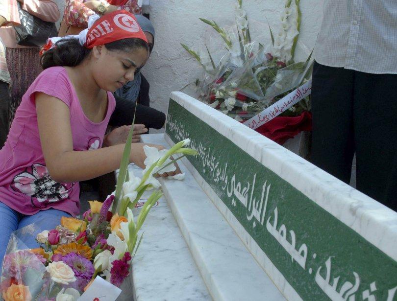 La fille deMohamed Brahmi se recueille sur un... (Photo SALAH HABIBI, AFP)