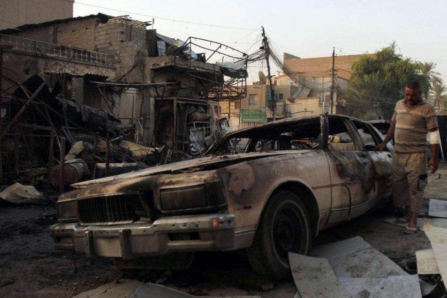 Un homme examine une voiture endommagée lors d'une... (PHOTO REUTERS)