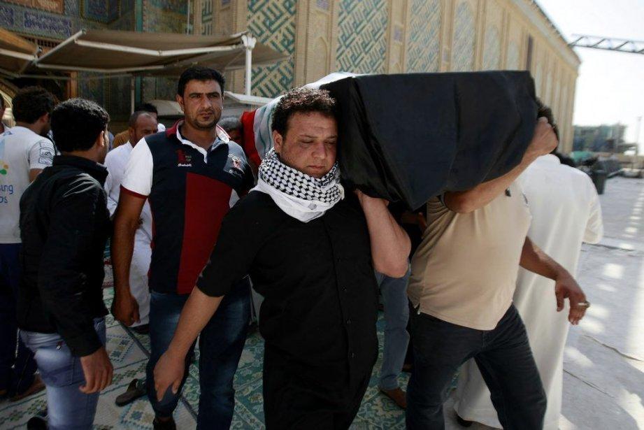 Des hommes transportent le cercueil d'une des victimes... (PHOTO ASSOCIATED PRESS)