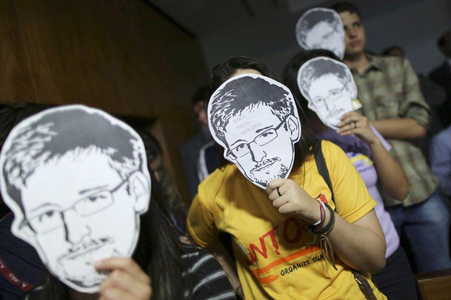 Des activistes brandissent des masques à l'effigie d'Edward... (PHOTO UESLEI MARCELLINO, ARCHIVES REUTERS)
