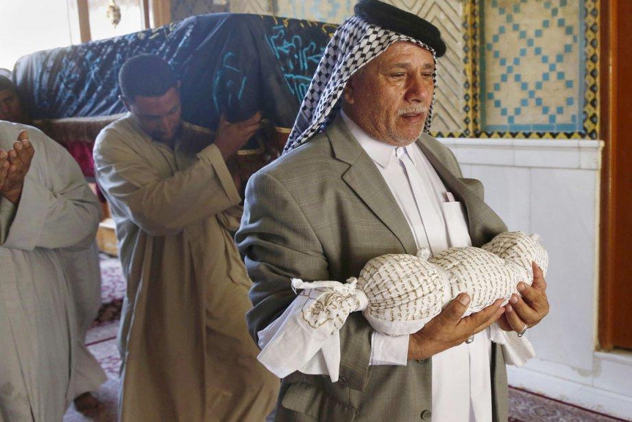 Un homme transporte la dépouille de son petit-fils... (PHOTO JABER AL-HELO, AP)