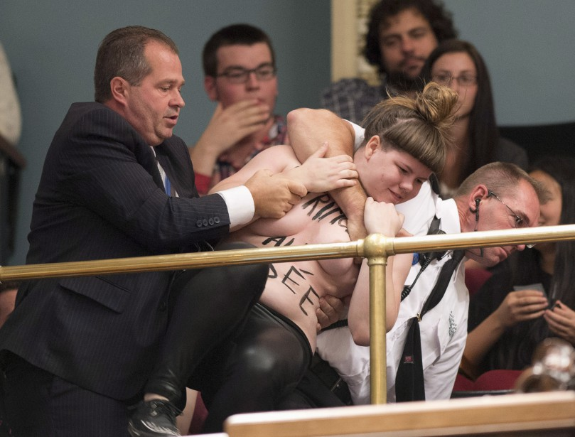 Une militante de Femen est interceptée après avoir... (Photo Jacques Boissinot, La Presse canadienne)