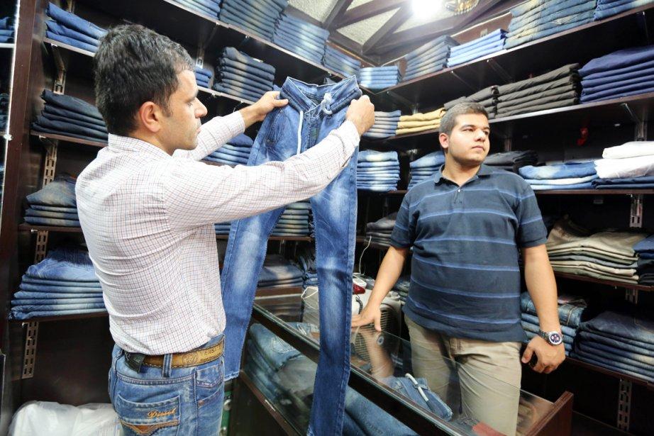 Un homme regarde une paire de jeans dans... (PHOTO ATTA KENARE, AFP)