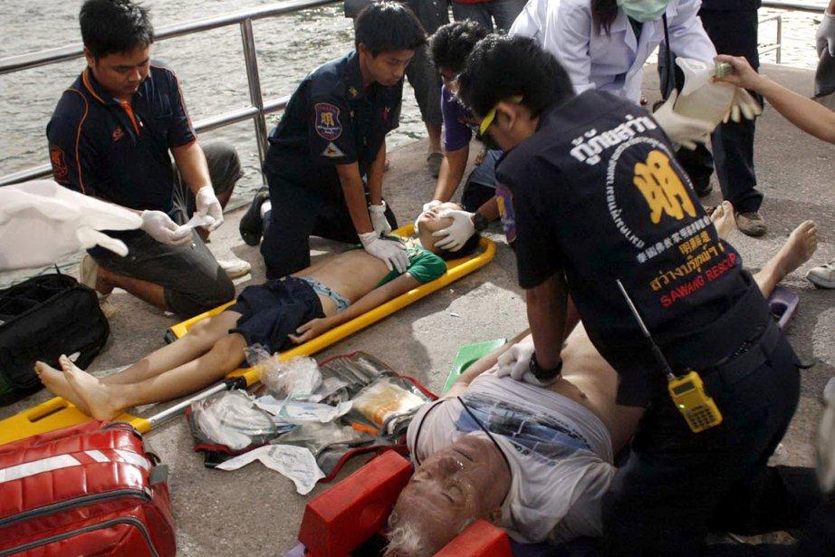Des secouristes administrent les premiers soins aux naufragés,... (PHOTO AGENCE FRANCE PRESSE)