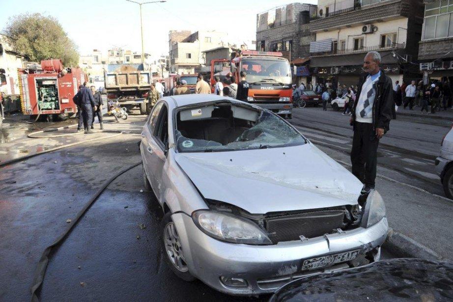 Un homme examine une voiture endommagée près d'une... (PHOTO SANA/AGENCE FRANCE PRESSE)