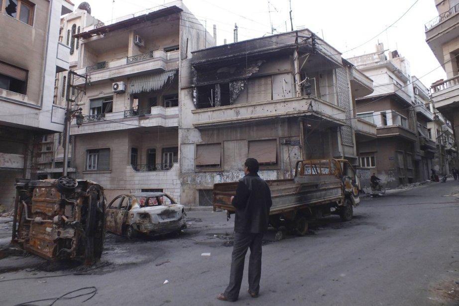 Un homme observe des véhicules endommagés par une... (PHOTO REUTERS)