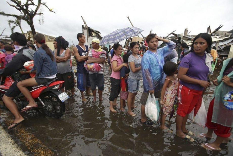 Des survivants font la file pour avoir des... (Photo Associated Press)