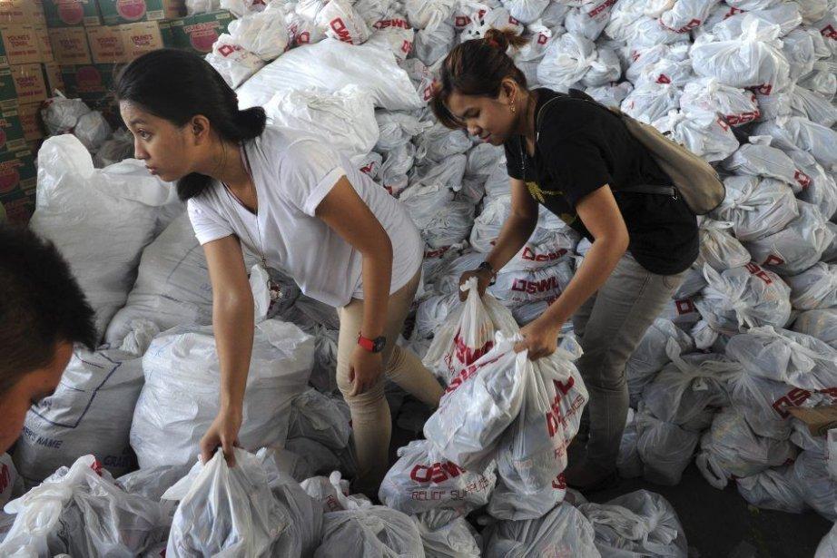 Des volontaires préparent des sacs de survie pour... (Photo AFP)