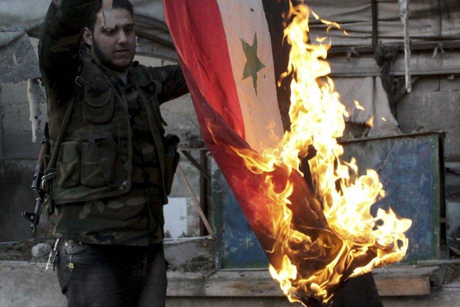 Un rebelle brûle un drapeau syrien trouvé dans... (PHOTO KARAM AL-MASRI, AGENCE FRANCE PRESSE)