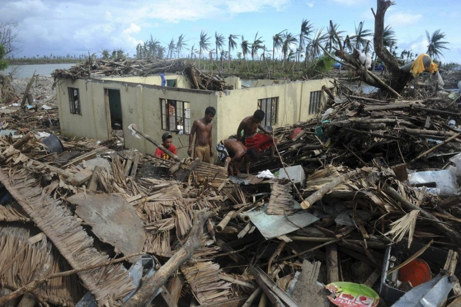 Des survivants recherchent du matérielrécupérable dans les décombres... (PHOTO NOEL CELIS, AGENCE FRANCE PRESSE)